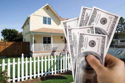 Casa con una mano al frente con dinero
